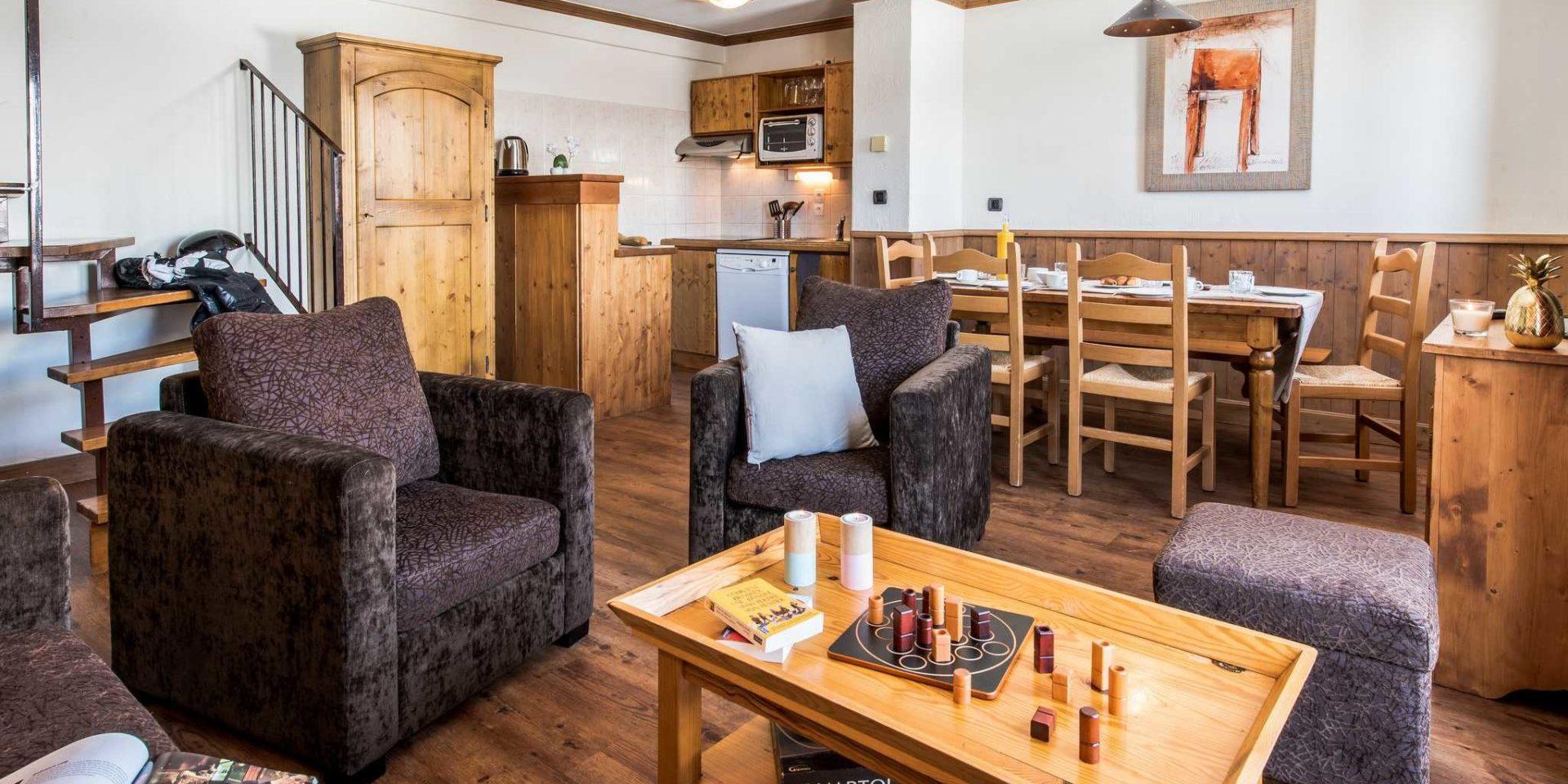 Residences Village Montana Tignes Tignes-Val d'Isere Frankrijk wintersport skivakantie luxe living 4K6 bruine fauteuils hocker salontafel gezelschapsspel kaarsen gedekte tafel houten stoelen schilderij hanglamp keuken trap