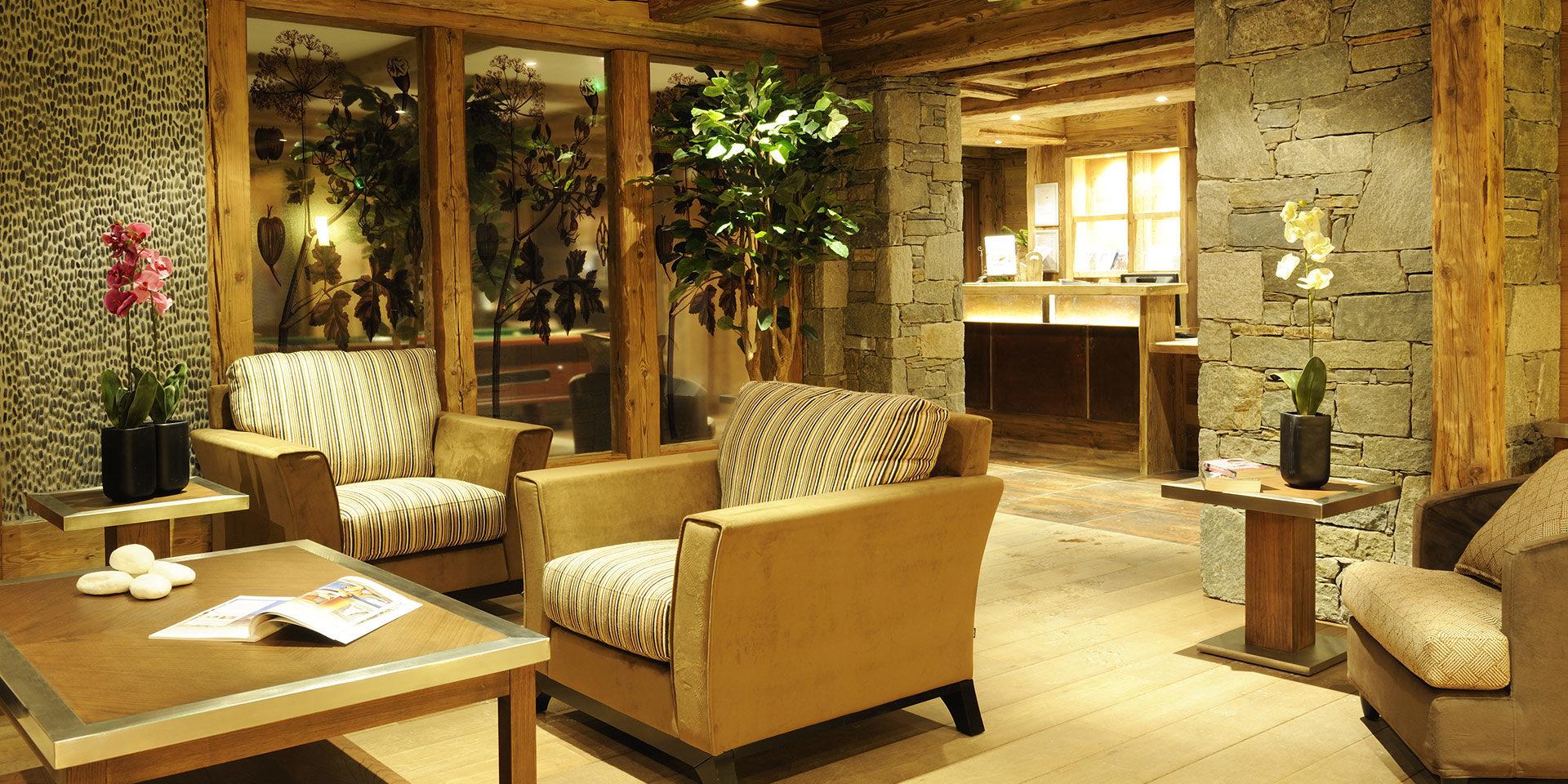 CGH L'Oree des Neiges Vallandry Paradiski Frankrijk wintersport skivakantie luxe receptie fauteuils Orchidee stenen muren hout planten raam