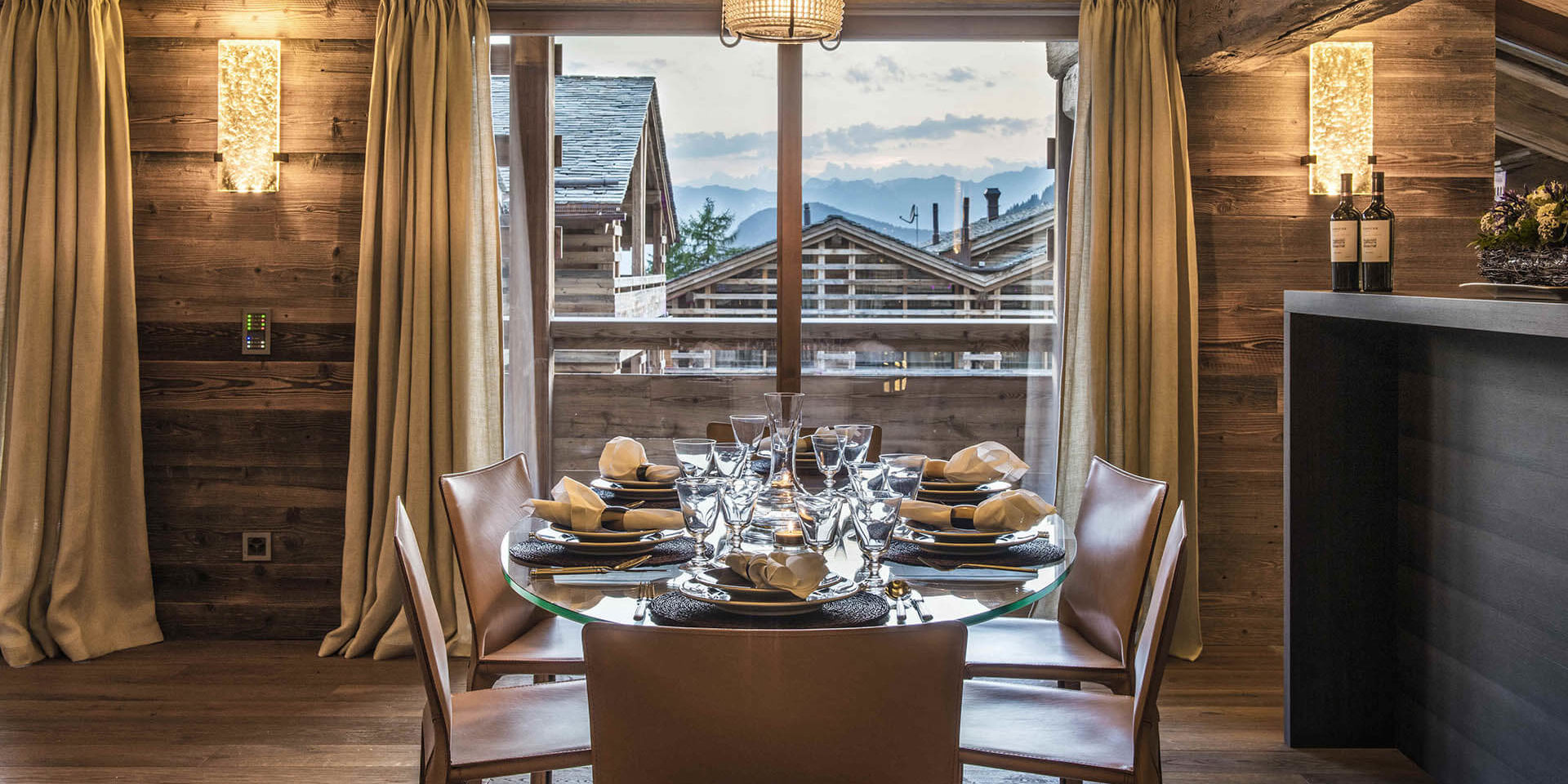 Appartement Place Blanche 2 Verbier Les 4 Vallees Zwitserland wintersport skivakantie luxe eetkamer gedekte tafel karaf hanglamp verlichting bar raam