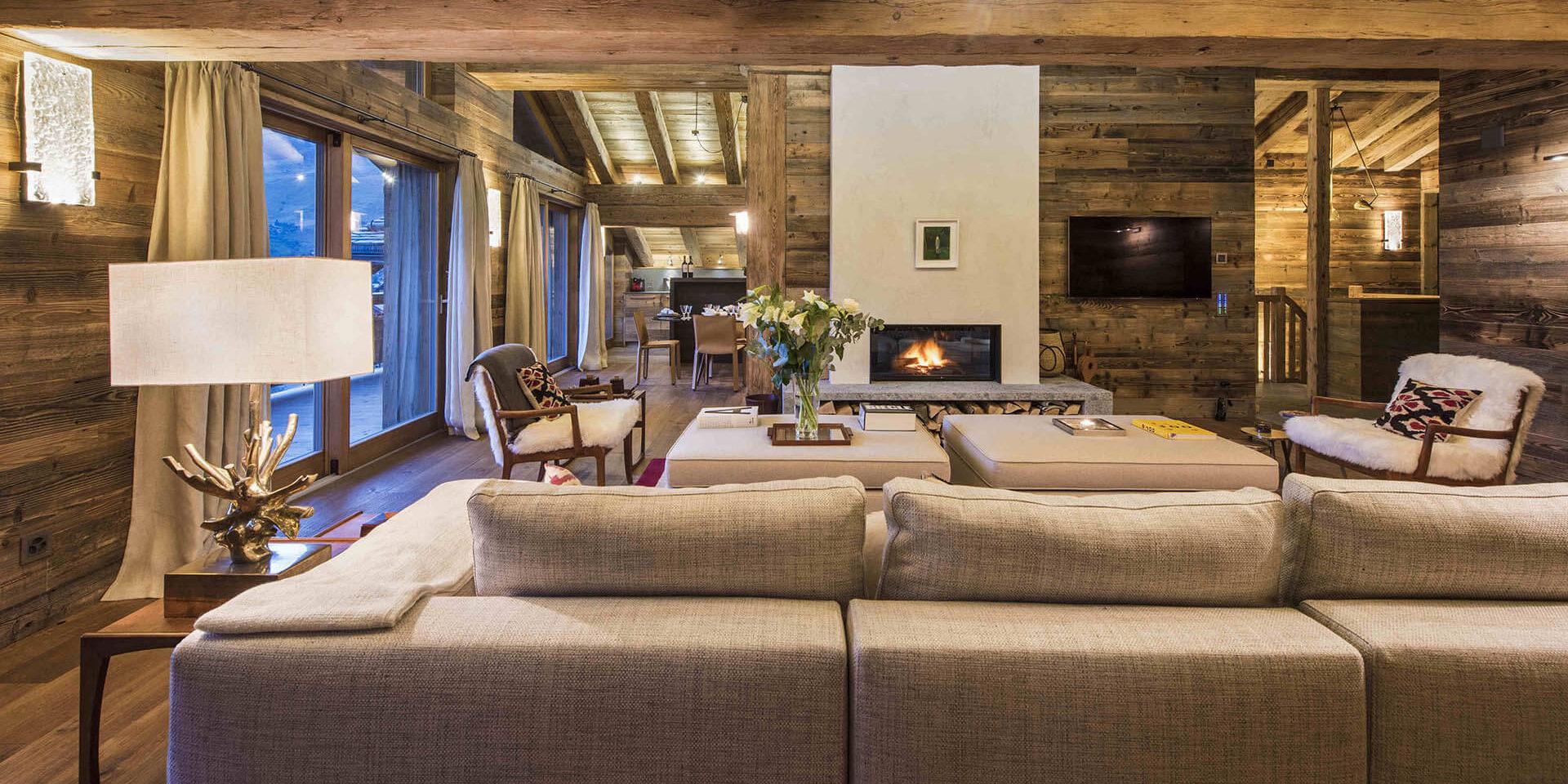 Appartement Place Blanche 2 Verbier Les 4 Vallees Zwitserland wintersport skivakantie luxe living bank fauteuils open haard hockers bloemen lamp houten balken