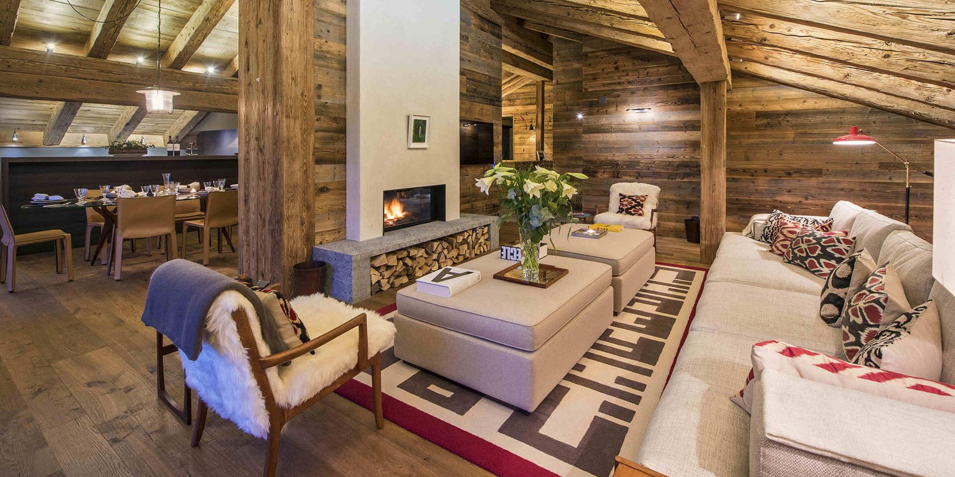 Appartement Place Blanche 2 Verbier Les 4 Vallees Zwitserland wintersport skivakantie luxe living bank fauteuils open haard hockers bloemen vloerkleed houten balken