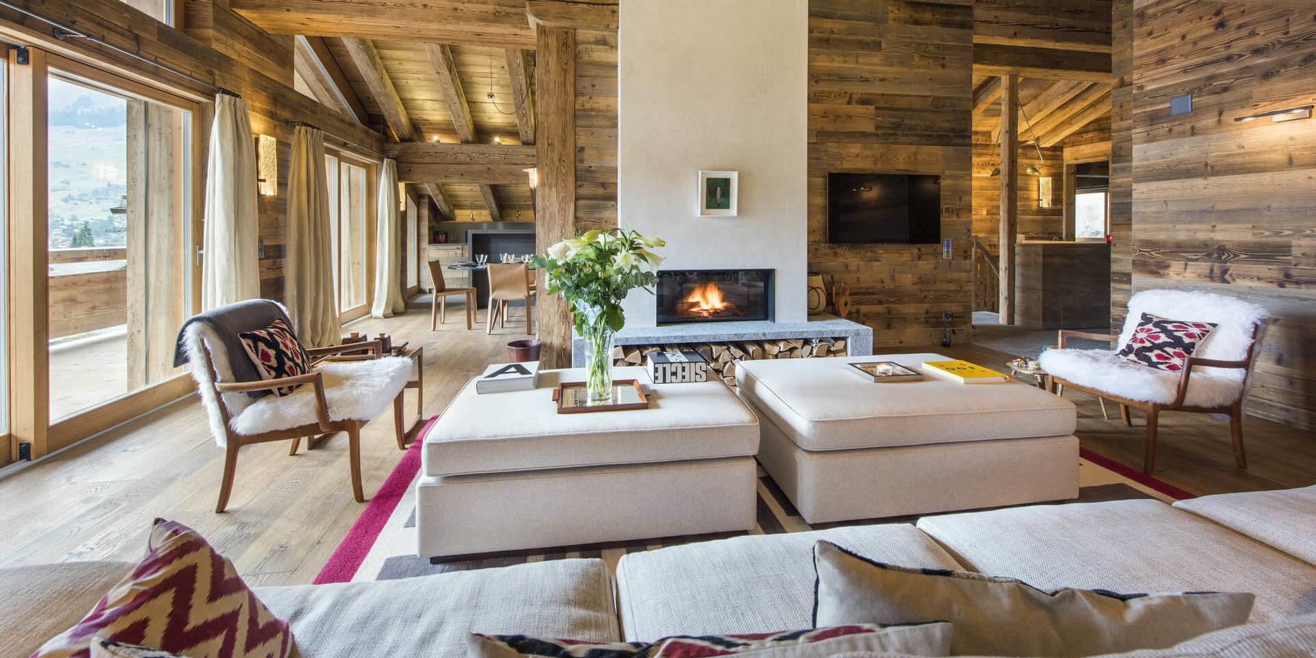 Appartement Place Blanche 2 Verbier Les 4 Vallees Zwitserland wintersport skivakantie luxe living fauteuils open haard hockers bloemen bank vloerkleed raam hout