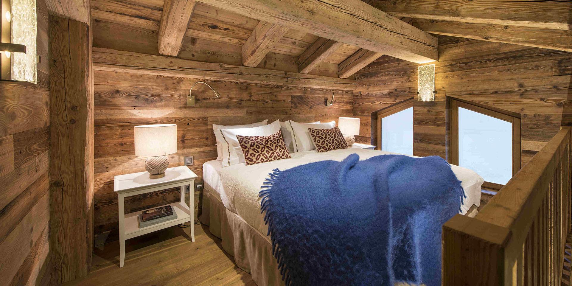 Appartement Place Blanche 2 Verbier Les 4 Vallees Zwitserland wintersport skivakantie luxe slaapkamer 2-persoonsbed nachtlampje schuin dak houten balken ramen