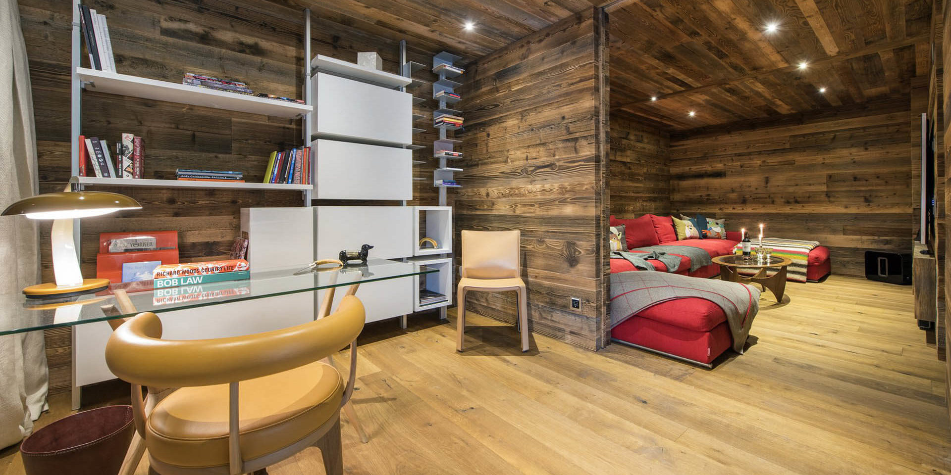 Appartement Place Blanche Verbier Les 4 Vallees Zwitserland wintersport skivakantie luxe TV kamer rode hoekbank bureau lamp kast boeken stoel hout