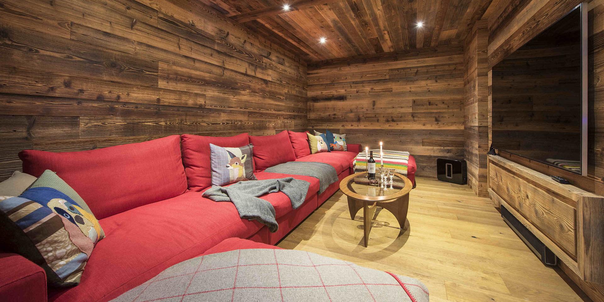Appartement Place Blanche Verbier Les 4 Vallees Zwitserland wintersport skivakantie luxe TV kamer rode loungebank kussens salontafel kaarsen verlichting hout