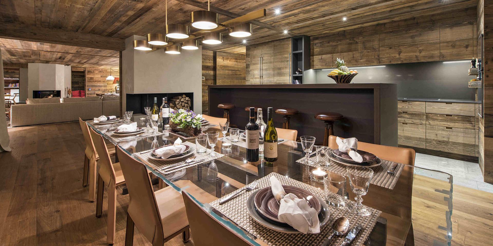 Appartement Place Blanche Verbier Les 4 Vallees Zwitserland wintersport skivakantie luxe eetkamer gedekte tafel wijn wijnglazen keuken bar fruit hout