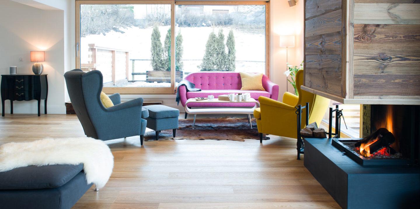 Chalet Rubicon Les Houches Chamonix Mont Blanc Frankrijk wintersport skivakantie luxe living zithoek open haard roze bank gele fauteuil blauwe fauteuil hocker vloerkleed ramen