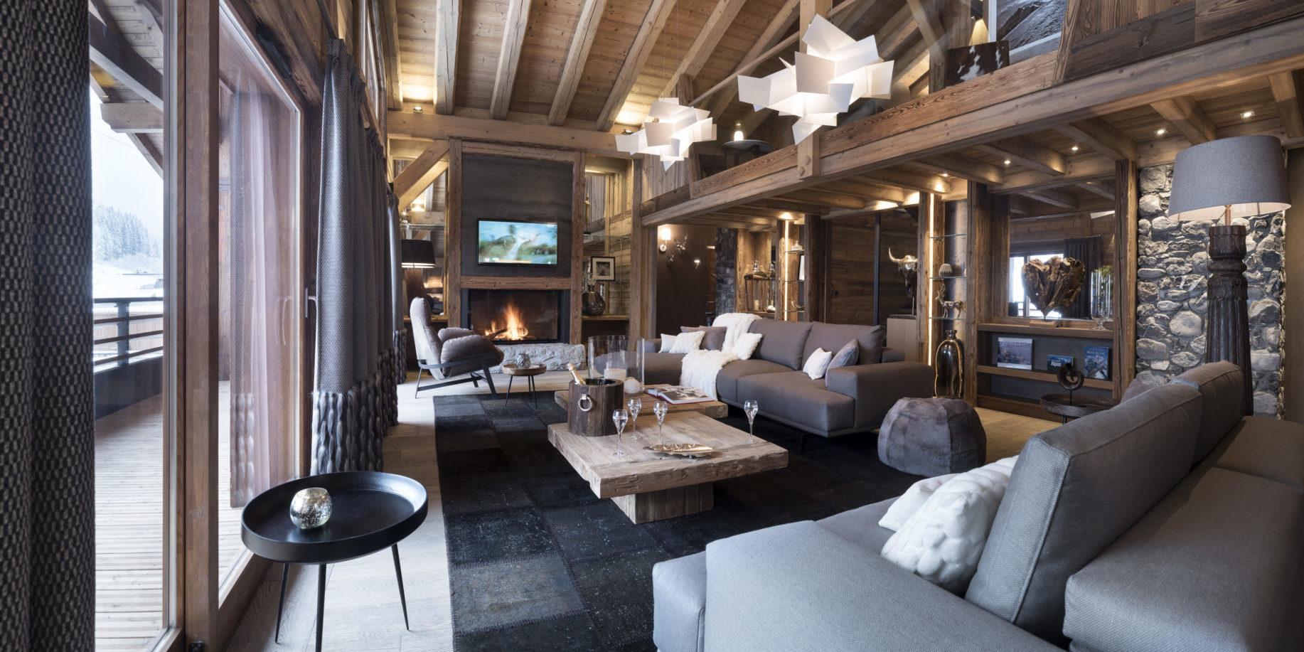 MGM L'Ecrin de Jade Chamonix Chamonix Mont Blanc Frankrijk wintersport skivakantie luxe living lounge banken fauteuil open haard vloerkleed hanglampen ramen houten balken