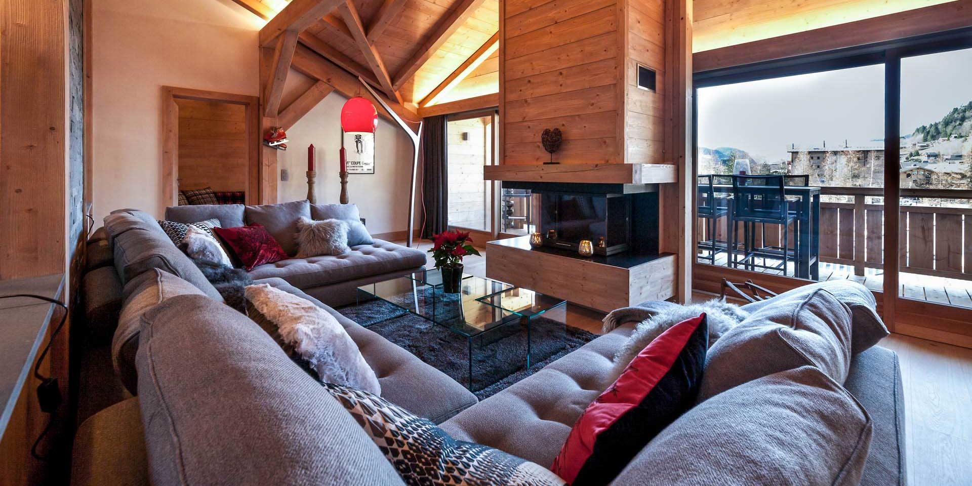 Penthouse Les Gets Les Portes du Soleil Frankrijk wintersport skivakantie luxe living loungebank open haard vloerkleed kaarsen balkon raam houten balken