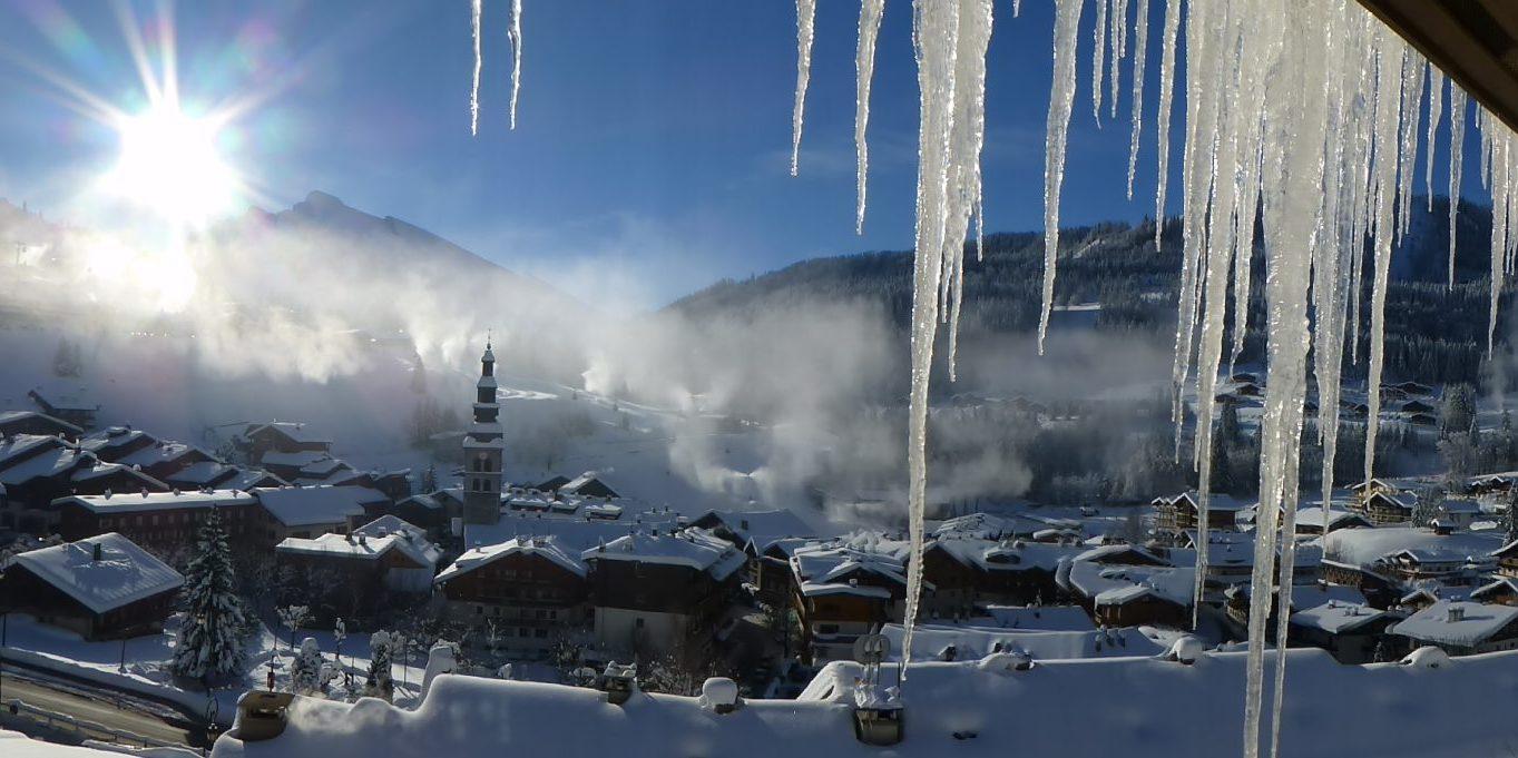 Residence Les Grandes Alpes La Clusaz Aravis Frankrijk wintersport skivakantie luxe uitzicht balkon dorp La Clusaz kerk besneeuwde bergen ijspegels sneeuw